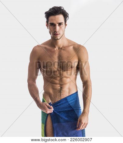 Portrait Of Naked Handsome Young Man With Languishing Look Covering Crotch With A Towel, Against Lig