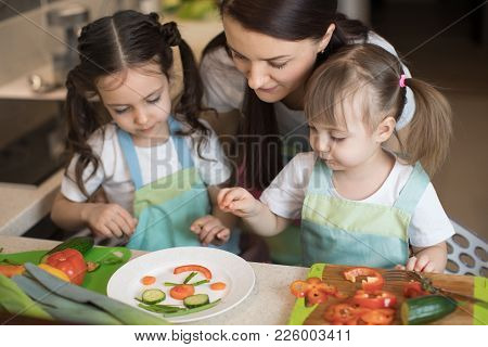 Happy Family Mother And Kids Daughters Are Preparing Healthy Food, They Improvise Together In The Ki