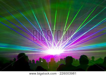 Laser Show Rays. Very Colorful Show With A Crowd Silhouette And Great Laser Rays On Pyrotechnic Fest
