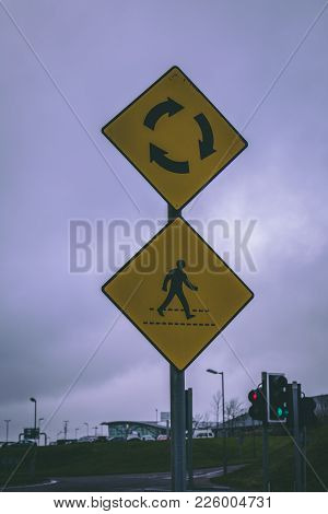 Close Up Of A Zebra Crossing And Roundabout Road Signs