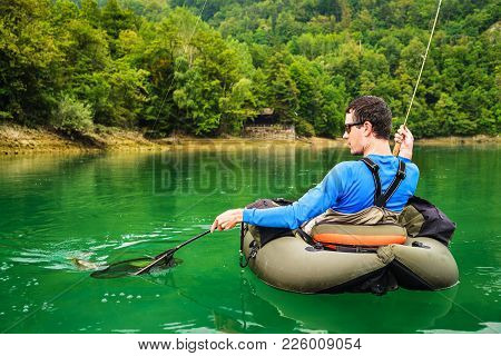 Fisherman Holding The Catch Of Rainbow Trout (oncorhynchus Mykiss) On Bellyboat, Jesenice, Slovenia.