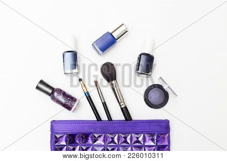 Female Cosmetic Bag And Cosmetics Of Purple Color On A White Background. Flat Lay