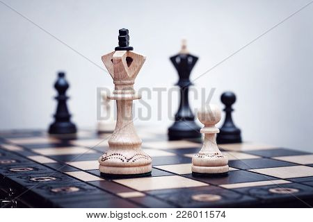 White Queen And Pawn Stand On A Chessboard In The Foreground Against A Background Of Blurred Black F