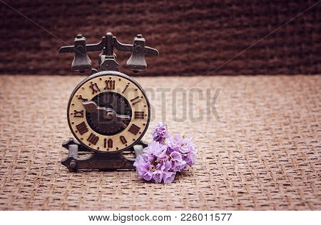A Souvenir Iron Watch With A Beige Dial Stand On A Sackcloth Stand Next To A Bouquet Of Purple Flowe
