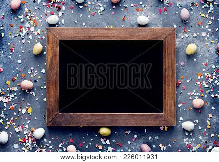 Easter Background - Blank Chalkboard In Wooden Frame On Table With Mini Candy Eggs And Colored Egg S