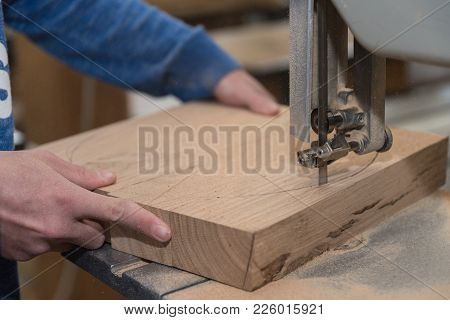 Carpenter Cuts Wood Piece With A Bench Saw - Close-up