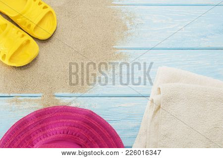 Yellow Flip Flops On White Beach Sand, Bright Hat And Towels
