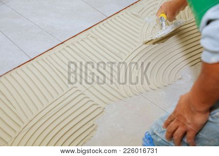 Master Puts Adhesive Spreading Wet Mortar Before Applying Tiles On Bathroom Floor.