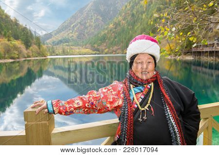 The Tibetan Woman Against Mountain Lake Of National Park Jiuzhaigou...