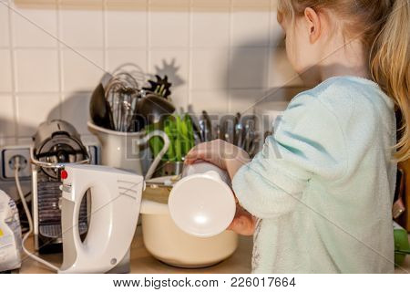 Little Girl Baking Waffles In The Kitchen At Home Following A Recipe On The Smartphone