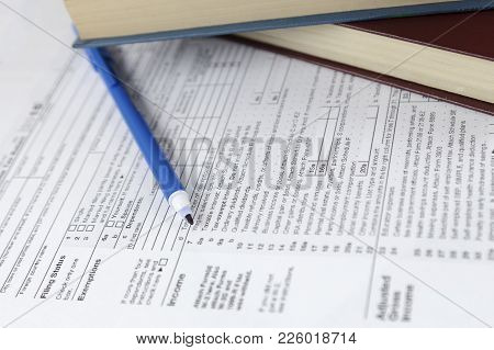 Individual Income Tax Return Form And Books Reports On Office Work Desk.
