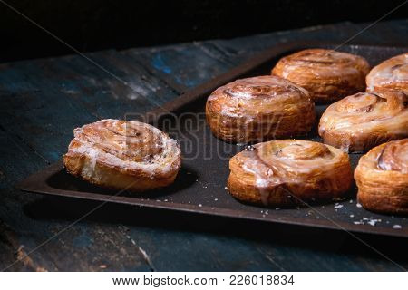 Homemade Glazed Puff Pastry Cinnamon Rolls With Custard And Raisins On Oven Tray Over Old Dark Blue