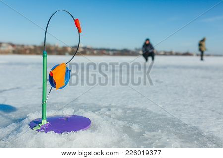 Winter Fishing, Fishing Rod Stands On The Hole Waiting For The Fish To Bite