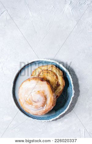 Homemade Glazed Puff Pastry Cinnamon Rolls With Custard And Raisins On Blue Plate Over Grey Texture