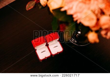 Rings Cartier In A Red Box On A Table With A Bouquet Of Flowers