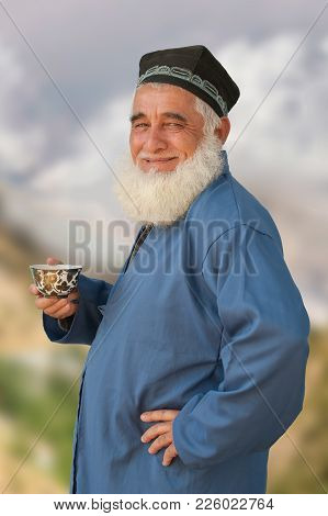 Photo Of A Distinguished Elderly Tajik With A White Beard On A Background Of Mountains