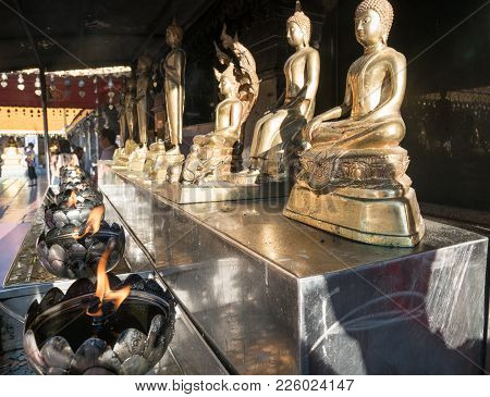 Chiang Mai, Thailand - January 26, 2017; Row Of Golden Buddha Statues On Bench With Flames Burning B