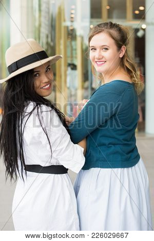 Closeup Portrait Of Two Young Beautiful Multiethnic Women Turning To Camera With Building In Backgro