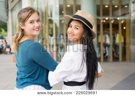 Closeup Portrait Of Two Young Beautiful Multiethnic Women Turning To Camera With Shop Window In Back