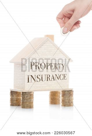 Wooden House Model Standing On Coins And Hand Holding The Coin With Conceptual Text. Property Insura