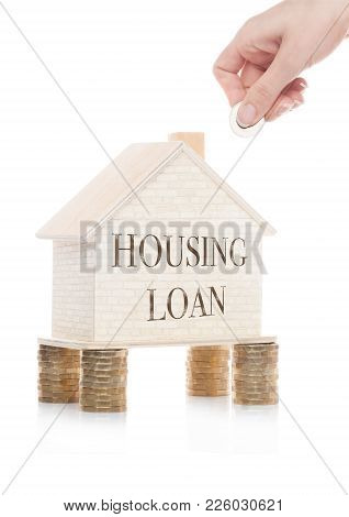 Wooden House Model Standing On Coins And Hand Holding The Coin With Conceptual Text. Housing Loan