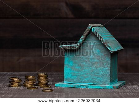 Wooden House Model With Coins Next To It With For Conceptual Text