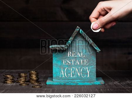 Wooden House Model With Coins Next To It And Hand Holding The Coin With Conceptual Text. Real Estate