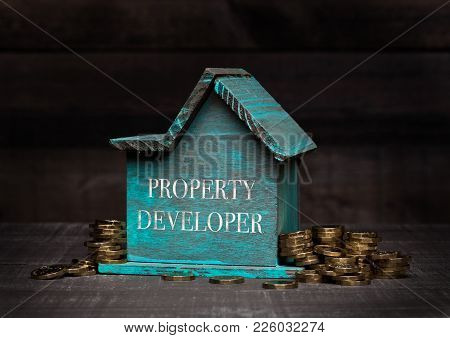 Wooden House Model With Coins Next To It With Conceptual Text. Property Developer