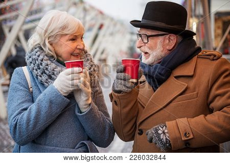 Happy Old Married Couple Is Drinking Mulled Wine While Standing Outdoor In Winter. They Are Looking