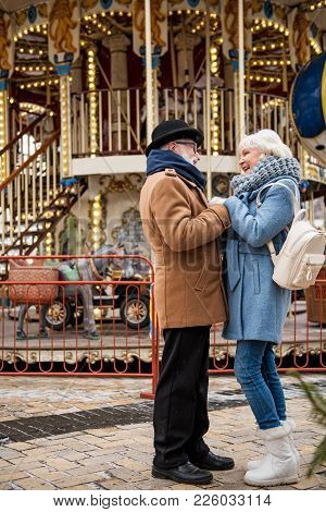 Full Length Of Cheerful Old Man And Woman Enjoying Romantic Date In City. Merry-go-round On Backgrou