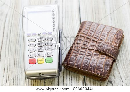 Modern Technology And People Concept - Pos Terminal And Purse. Rough Bords Background. Closeup