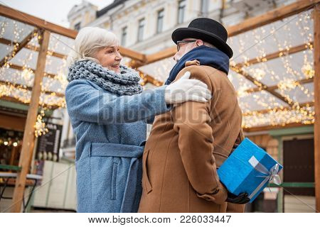 Happy Romantic Old Married Couple Is Celebrating Anniversary. Man Is Hiding Gift Box Behind His Back