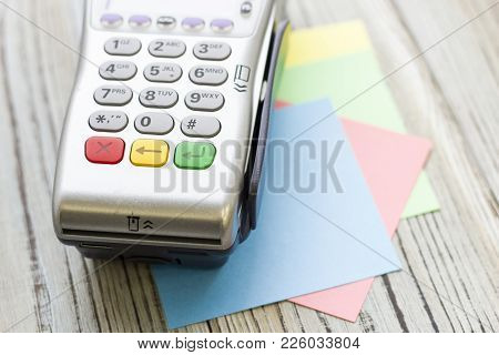 Modern Technology And People Concept - Pos Terminal. Rough Bords Background. Closeup