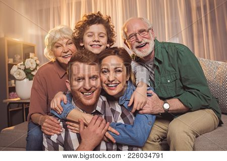 Portrait Of Cheerful Wife Hugging Smiling Unshaven Husband. Glad Grandparents With Grandson Looking