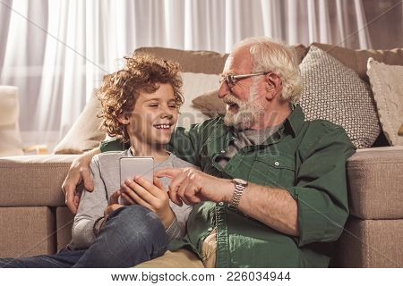 Happy Granddad And Beaming Grandson Talking While Holding Mobile In Hand. Leisure Concept