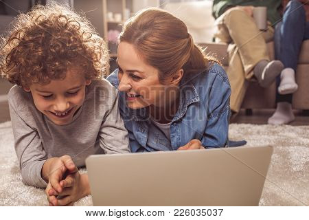 Happy Kid And Beaming Mother Watching At Notebook Computer While Locating On Carpet. Appliance Conce