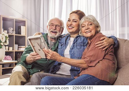 Portrait Of Cheerful Bearded Grandpa, Cheerful Daughter And Beaming Wife Holding Frame. They Looking