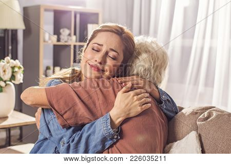 Portrait Of Smiling Woman Hugging Granny In Room. They Locating In Apartment. Family Concept