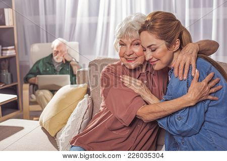 Outgoing Granny Embracing Cheerful Adult Daughter While Sitting On Sofa. Granddad Typing In Laptop.