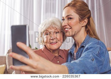 Portrait Of Smiling Grandmother And Happy Daughter Creating Photo By Mobile. Family Concept