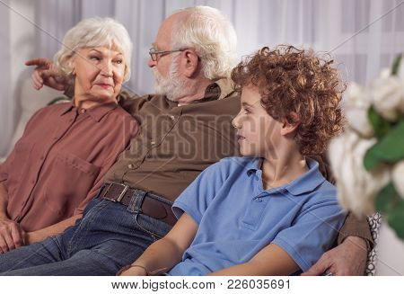 Happy Grandmother Talking With Bearded Grandpa While Sitting In Room. Smiling Little Grandson Listen