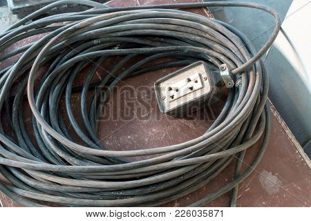 A White Extension Power Cord With A Very Long Cable For Construction Use. Industry Concept.