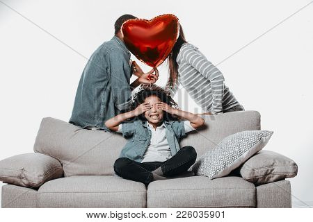Young Parents Putting Out Of Sight Her Faces With Air Heart And Their Content Daughter Sitting And H