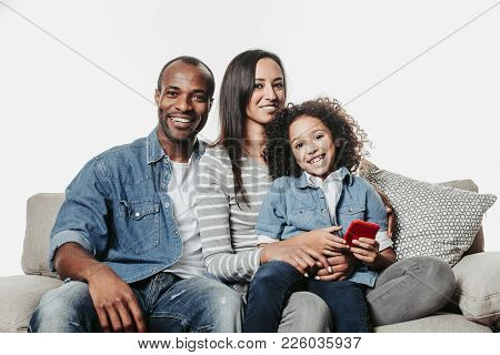 Portrait Of Laughing Mom, Daddy And Child With Device In Hand Spending Free Time With Comfort. They