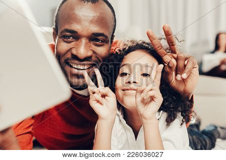 Laughing Dad And Child Making Selfie On Tab Together. They Are Smiling And Showing Two Fingers Gestu