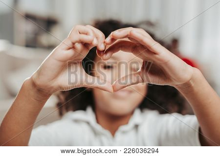 Amour Concept. Smiling Kid Showing Her Love With Gesture. Focus On Hands