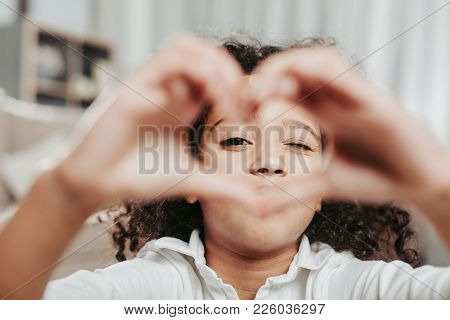 Love Concept. Calm Girl Peeping Through Love Gesture Made With Her Fingers. Focus On Face