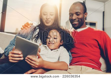 Low Angle Portrait Of Amused Mom, Dad And Child Relaxing Together In Comfortable House And Using Gad