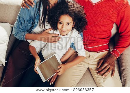 Top View Portrait Of Satisfied Girl Sitting On Sofa With Their Parents. She Is Holding Tab In Hands