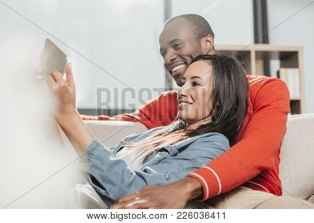 Happy Family Enjoying Weekend Together Indoors. They Are Looking At Tablet And Smiling